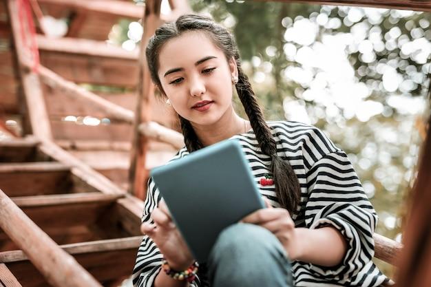 Активный обмен сообщениями. веселая азиатская женщина с улыбкой на лице, глядя на экран планшета