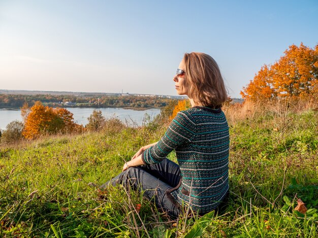 An active middle-aged blonde woman in sunglasses is relaxing sitting on a hill with beautiful views
