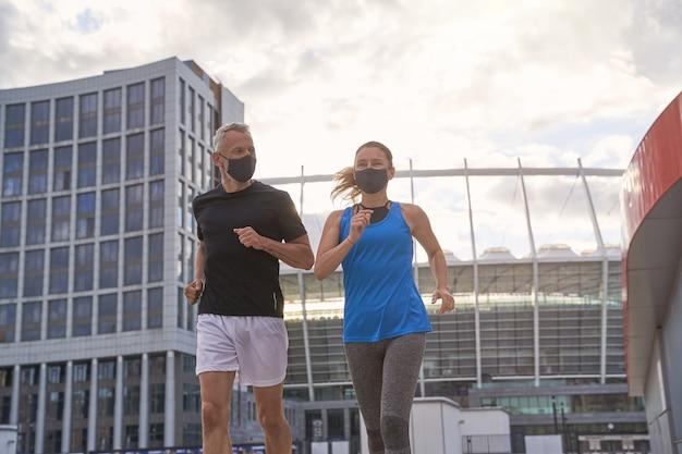 Активная пара среднего возраста в защитных масках вместе бегает по утрам в городской среде