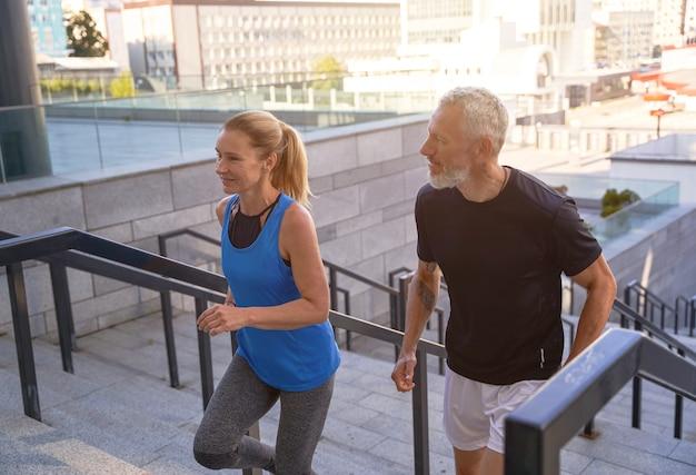 운동복 차림의 활동적인 중년 부부는 운동하는 동안 도시에서 계단을 오르고 있다