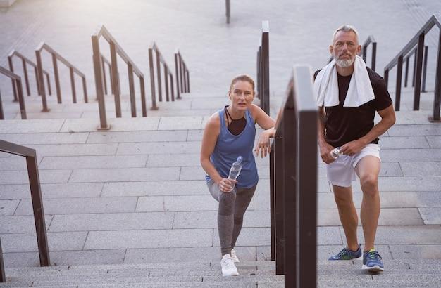 Активная пара среднего возраста мужчина и женщина в спортивной одежде, глядя в камеру, поднимаясь по лестнице после