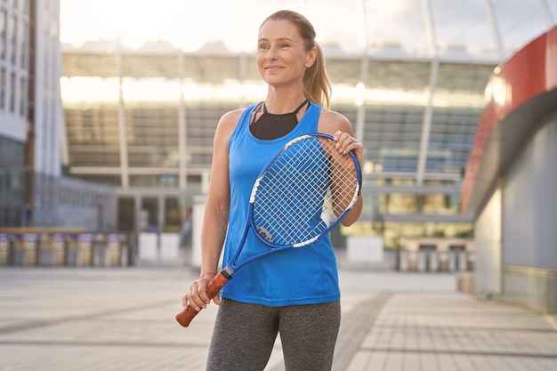 Active middle aged woman holding tennis racket ready for playing tennis outdoors training in the