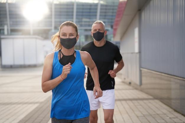 Активная женщина средних лет в защитной маске во время бега вместе с мужем на открытом воздухе