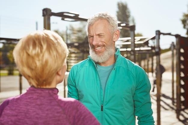 활동적인 아침 행복한 노인 가족 커플이 야외에서 스포츠를 하고 있습니다. 스포츠웨어를 입은 성숙한 수염 난 남자