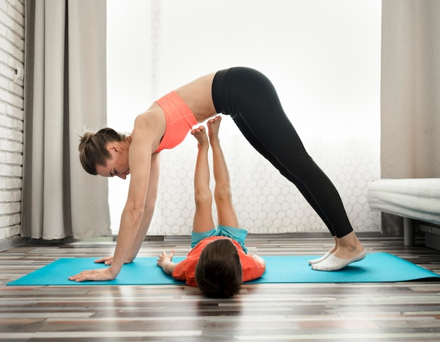 Active mother exercising with son at home