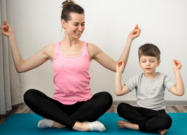 息子と一緒にヨガの練習をするアクティブな母親