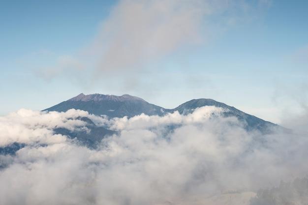 인도네시아 카와 이젠(kawah ijen)의 아침 안개와 푸른 하늘에 활화산