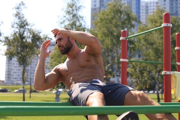 Активный мускулистый спортсмен делает тренировку пресса и скручивания на открытом воздухе, тренируется.