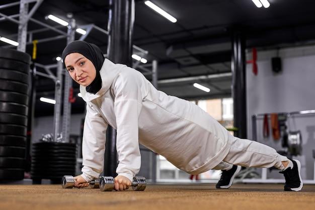 Активная мусульманка в хиджабе, интенсивно тренируясь, делает планку отжиманий с гантелями. кроссфит упражнения в тренажерном зале, спортивная концепция