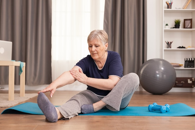 Активная старуха тренируется на коврике для йоги в своей комфортабельной квартире