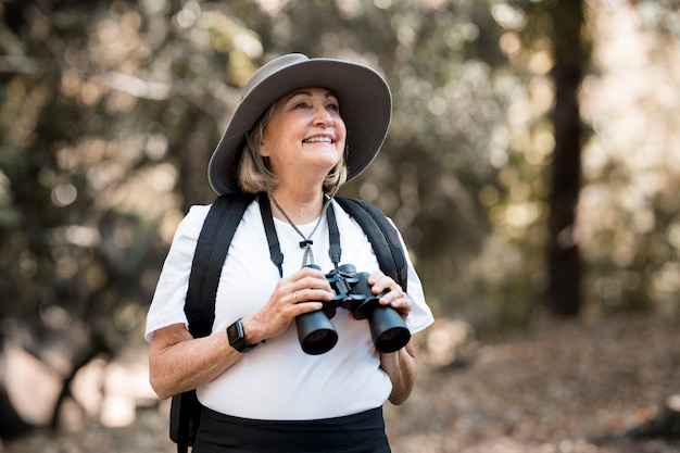 Active old woman using binoculars to see the beauty of nature