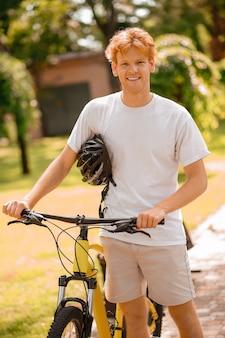 Активное времяпрепровождение. рыжий улыбающийся парень в белой футболке с велосипедом в шлеме на прогулке на свежем воздухе в летний день