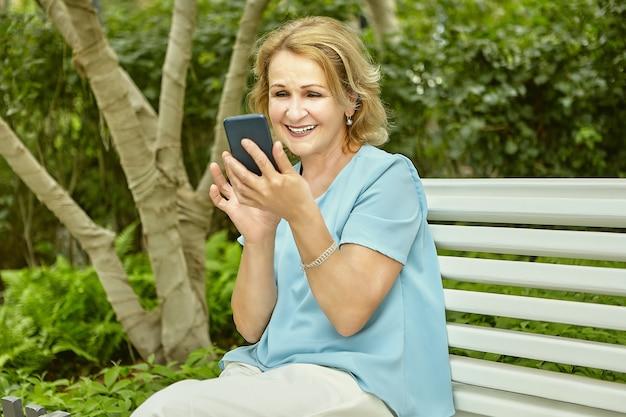 손에 휴대 전화와 약 60 세 활성 연금 매력적인 백인 여자는 공공 공원에서 벤치에 앉아있다.