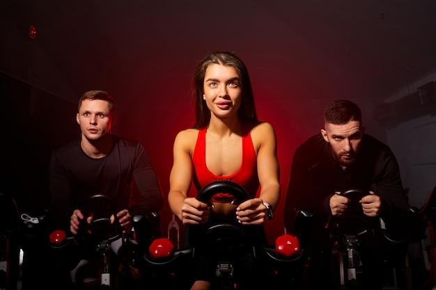 어두운 연기가 자욱한 공간에서 운동복을 입고 자신있게 기대하며 체육관에서 스포츠 장비를 훈련하는 활동적인 사람들