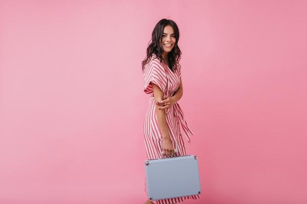 Bruna attiva e positiva va in aeroporto con il bagaglio a mano. ritratto di ragazza abbronzata in prendisole a strisce.