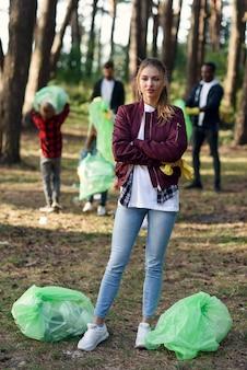 森でゴミ拾いをしている友達のボランティアを背景に、ゴミ袋がいっぱい入ったアクティブな可愛い女の子。