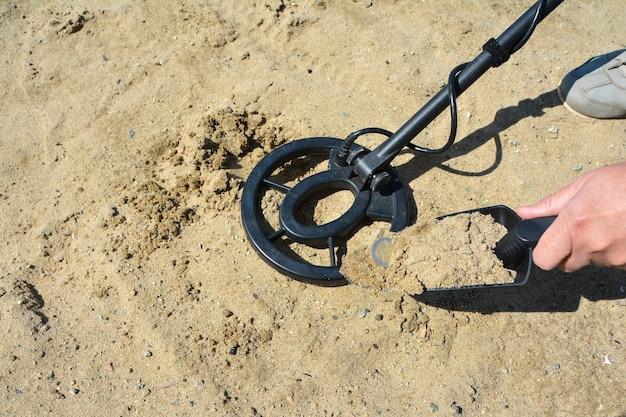 Активный отдых и увлечения мужчина нашел монету в песке с помощью металлоискателя.