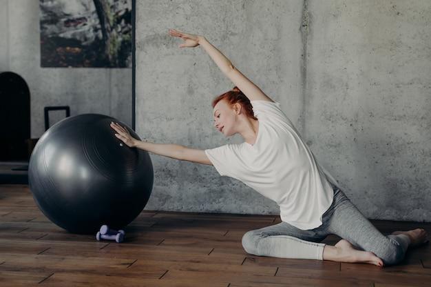 필라테스 스튜디오의 콘크리트 회색 벽 옆 쪽모이 세공 마루 바닥에 맨발로 앉아 있는 동안 핏볼로 스트레칭 운동을 하는 활동적인 빨간 머리 피트니스 소녀. 활동적인 라이프 스타일과 바디 케어 개념