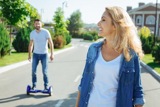적극적인 휴식. 행복 한 낙관적 인 여자 웃 고 그녀의 뒤에 자체 균형 스쿠터를 타고 그녀의 쾌활 한 남편을 선회