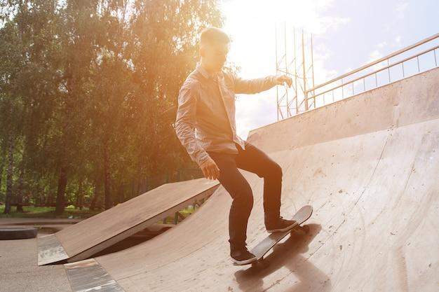 スケートパークでのアクティブな休息。シャツとジーンズのuteguyヒップスターは、木々と明るい日光を背景に公園でスケートボードのスライドに乗っています