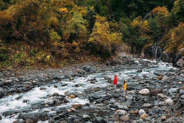 자연에 대한 적극적인 휴식. 가 산 강을 따라 산책 하는 두 명의 관광객. 활동적인 커플이 하이킹에 종사하고 있습니다. 젊은 부부가 추적에 종사하고 있습니다. 복사 공간