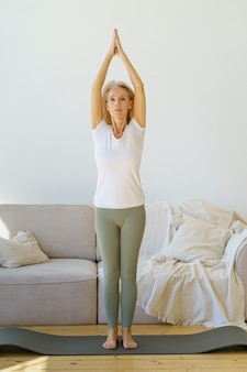 Active retired mature woman doing yoga exercise surya namaskar in living room at home
