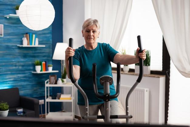 健康のためにテレビでフィットネスビデオを見ているサイクリング自転車マシンを使用して脚の筋肉を働いているアクティブな退職年配の女性。健康有酸素運動中に体を動かす年金受給者
