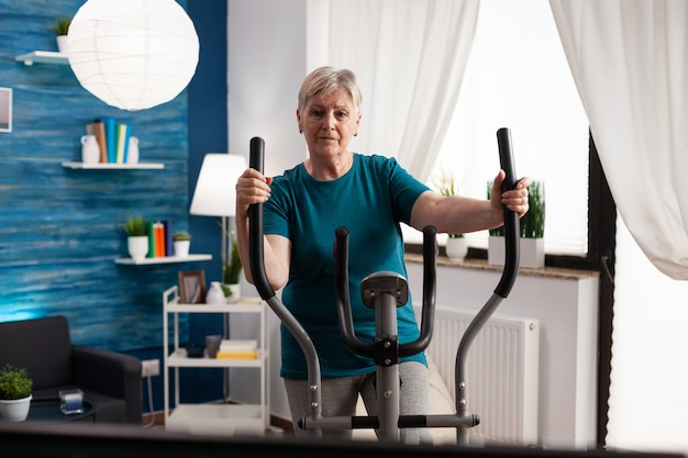 Active retirement senior woman working legs muscle using cycling bicycle machine watching fitness video on television for well being. pensioner doing body exercise during health cardio workout