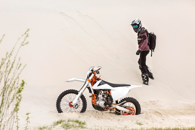 Активный гонщик наблюдает за своим мотоциклом в пустыне