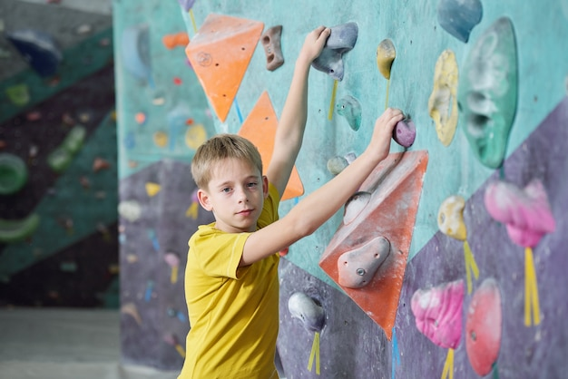 Active schoolboy in yellow t-shirt grabbing by artificial rocks on climbing wall while training in contremporary sports center