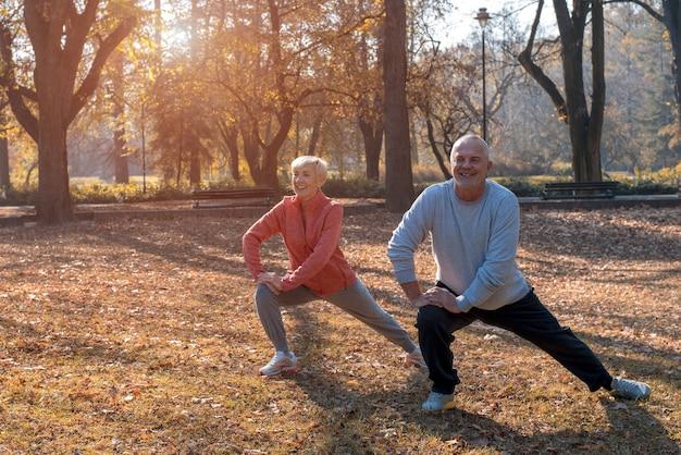 화창한 날 공원에서 야외 운동을 하는 활동적인 노부부