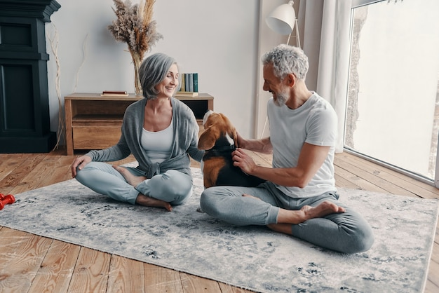 自宅で時間を過ごしながら運動と笑顔のスポーツウェアのアクティブな年配のカップル