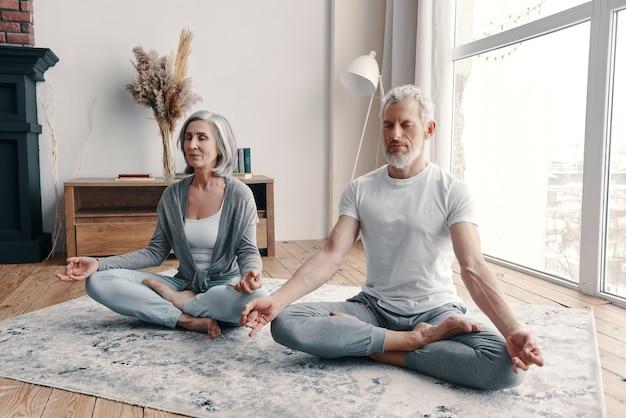 一緒に家で運動するスポーツウェアのアクティブな年配のカップル