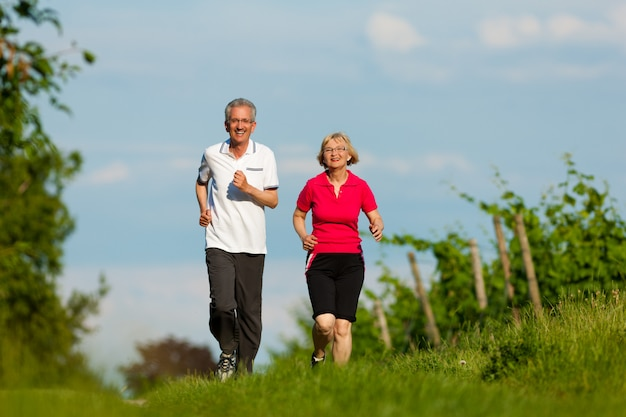Active senior couple jogging along a country road