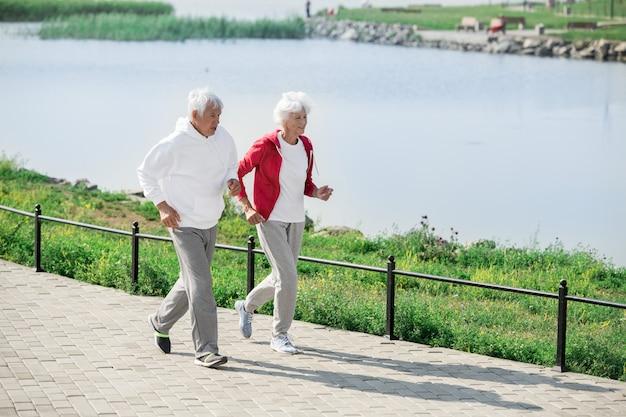 Active senior couple jogging by lake