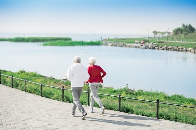 Active senior couple running along lake