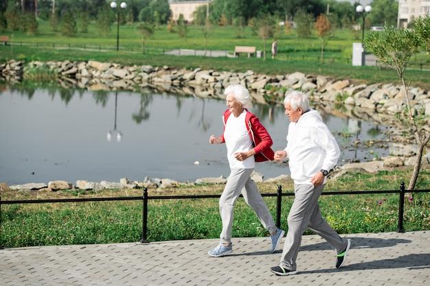 Active senior couple running by lake