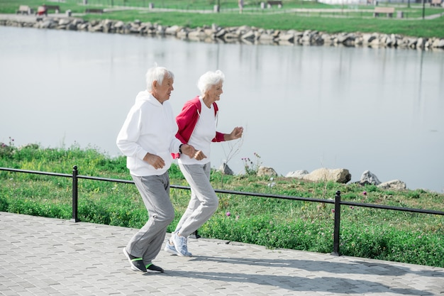Active senior couple running by pond