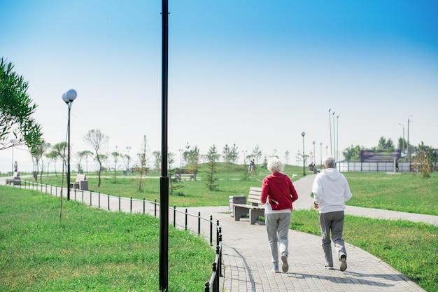 公園で実行されているアクティブな年配のカップルの背面図