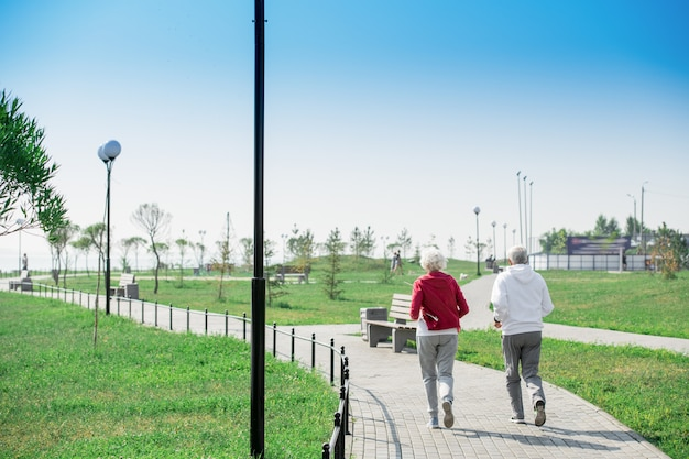 Active senior couple running in park back view