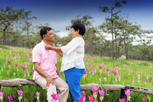 一緒に活動的なシニアカップルは、ピンクの花畑でロマンチックな楽しみ