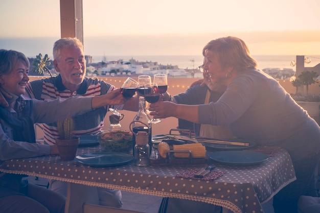 도시와 바다를 볼 수있는 테라스에서 집에서 함께 저녁 식사를하는 성숙한 친구의 그룹과 활성 수석 노인 개념