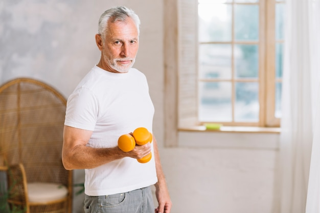 Active senior man exercising with dumbbells