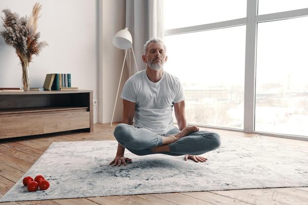 自宅でヨガの位置で手に立っている間瞑想するスポーツ服のアクティブな年配の男性
