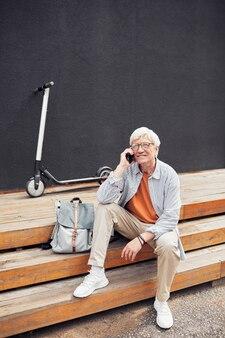 Активный старший мужчина разговаривает по смартфону в городе