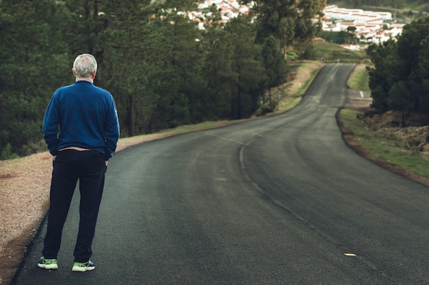 Active senior man standing on lonely road between mountains