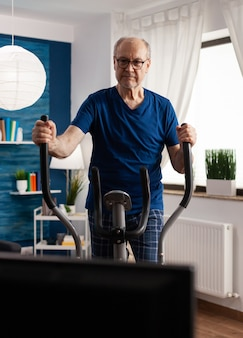 Active senior man training legs muscle resistance cycling bicycle machine in living room during life...