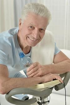 Active senior man with bike in gym
