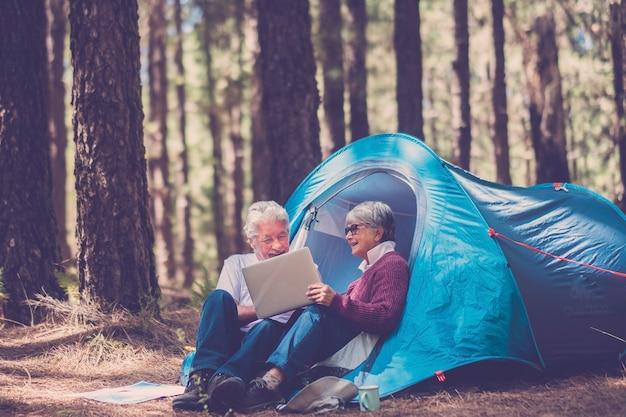 アクティブな高齢者は、ラップトップコンピュータを使用して、無料の森の風景の中で屋外でテントキャンプを楽しんでいます-森のキャンプでの屋外レジャー活動の高齢者の成熟した男性と女性
