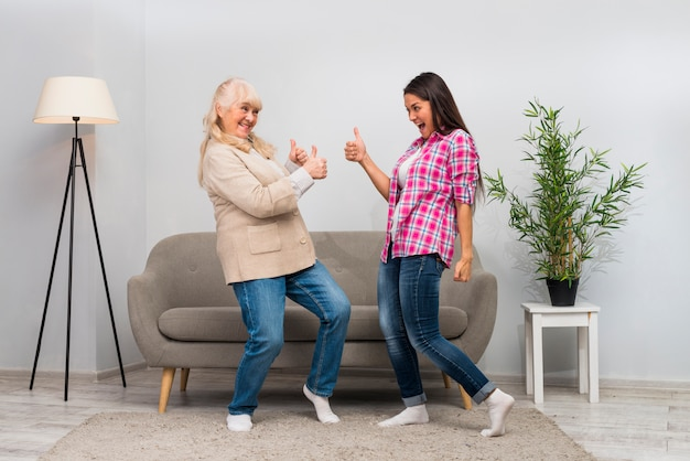 Active senior woman and her young daughter showing thumb up sign to each other in the living room